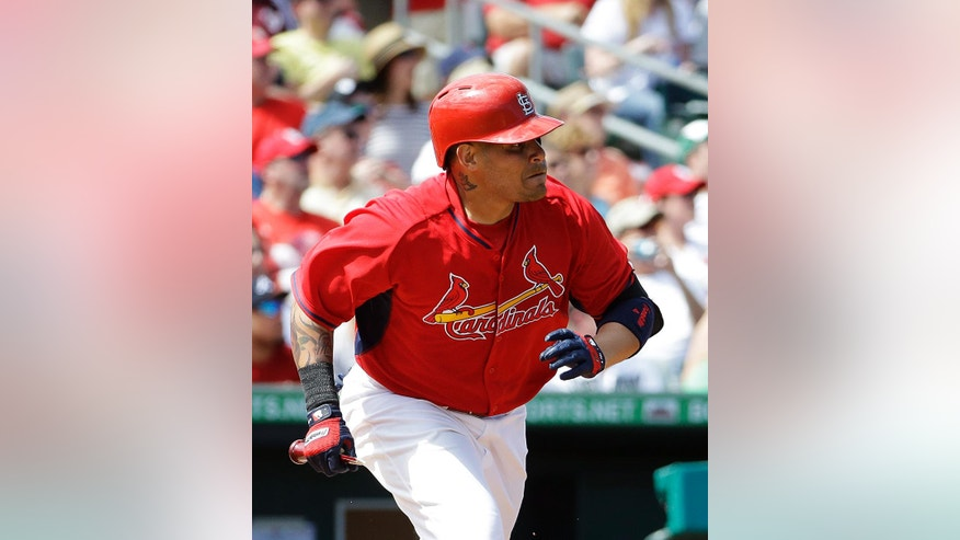 St. Louis Cardinals' Yadier Molina hits a single in the second inning of an exhibition spring training baseball game against the Washington Nationals, Saturday, March 8, 2014, in Jupiter, Fla. (AP Photo/David Goldman)