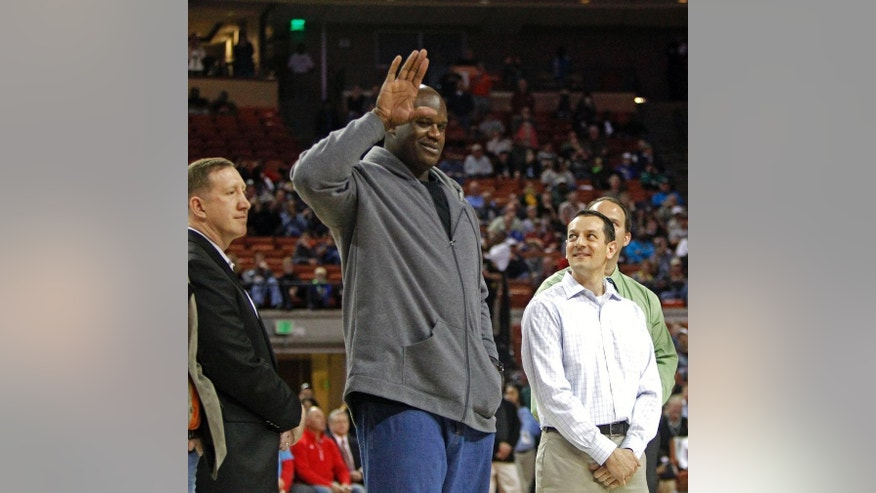 Former NBA star Shaquille O'Neal waves to the crowd while standing with his former high school teammates during halftime of the boys' UIL Class 1A Division 1 state basketball final, Saturday, March 8, 2014, in Austin, Texas. The UIL was honoring the undefeated 1989 San Antonio Cole Team (36-0) that won the state championship 25 years ago.  O'Neal was described as the greatest player to ever play in the UIL State Tournament by UIL Executive President Charles Breithaupt. (AP Photo/Michael Thomas)