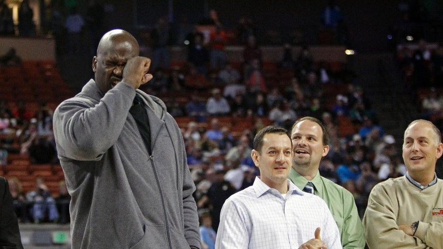 Former NBA star Shaquille O'Neal feigns crying during his introduction while standing with his former high school teammates during halftime of the boys' UIL Class 1A Division 1 state basketball final, Saturday, March 8, 2014, in Austin, Texas. The UIL was honoring the undefeated 1989 San Antonio Cole Team (36-0) that won the state championship 25 years ago.  O'Neal was described as the greatest player to ever play in the UIL State Tournament by UIL Executive President Charles Breithaupt. (AP Photo/Michael Thomas)