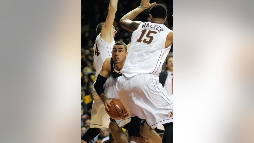 Penn State's Jordan Dickerson, center, attempts to get to the basket between Minnesota's Maurice Walker, right, and Joey King during the first half of an NCAA college basketball game on Sunday, March 9, 2014, in Minneapolis. (AP Photo/Tom Olmscheid)