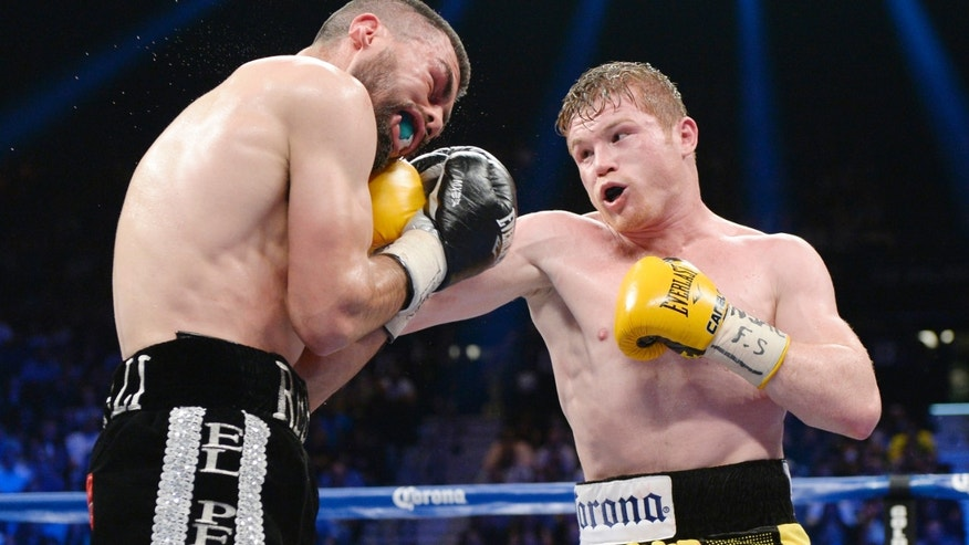 LAS VEGAS, NV - MARCH 8: Canelo Alvarez throws a punch against Alfredo Angulo (L) during the non-title, 12-round super welterweight bout at the MGM Grand Garden March 8, 2014, in Las Vegas, Nevada. Alvarez won by technical knock out after the referee stopped the fight in the 10th round. (Photo by Kevork Djansezian/Getty Images)
