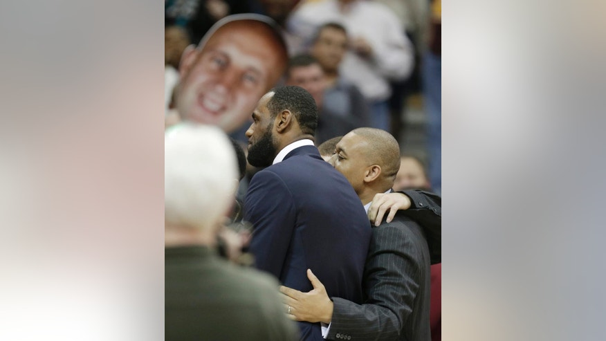 LeBron James, center left, hugs former players and coaches after Zydrunas Ilgauskas' jersey was retired during a halftime ceremony at an NBA basketball game between the New York Knicks and the Cleveland Cavaliers on Saturday, March 8, 2014, in Cleveland. (AP Photo/Tony Dejak)