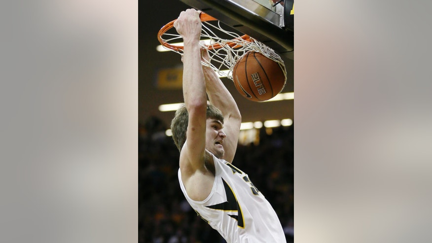 Iowa center Adam Woodbury dunks the ball during the first half of an NCAA college basketball game against Illinois, Saturday, March 8, 2014, in Iowa City, Iowa. (AP Photo/Charlie Neibergall)