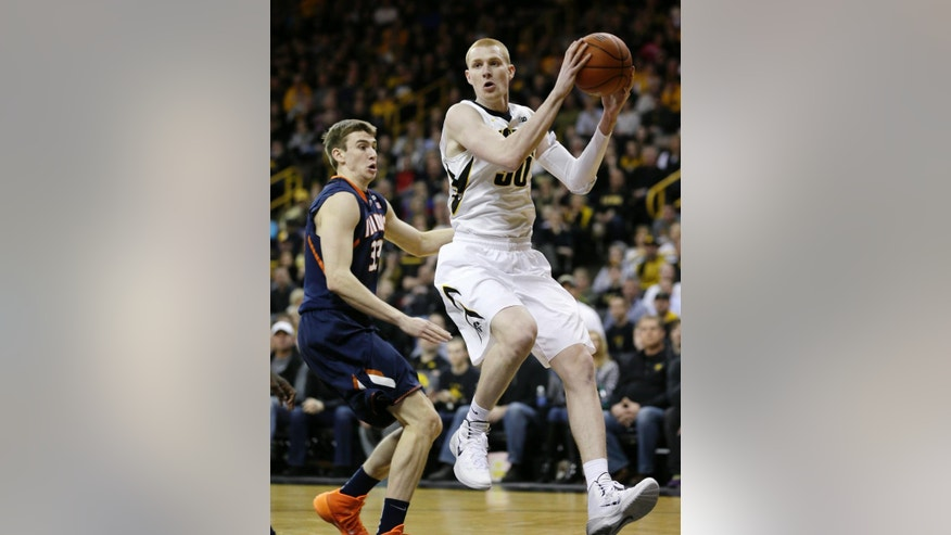 Iowa forward Aaron White, right, drives to the basket past Illinois forward Jon Ekey during the first half of an NCAA college basketball game on Saturday, March 8, 2014, in Iowa City, Iowa. (AP Photo/Charlie Neibergall)
