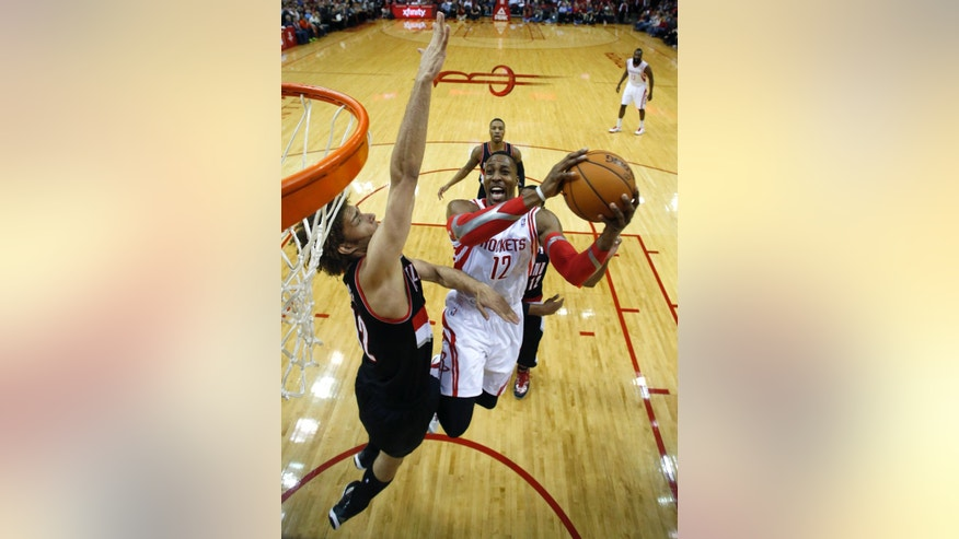 Houston Rockets' Dwight Howard (12) goes up to shoot as Portland Trail Blazers' Robin Lopez defends during the first quarter of an NBA basketball game on Sunday, March 9, 2014, in Houston. (AP Photo/David J. Phillip)