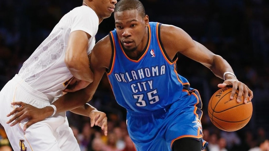 Oklahoma City Thunder small forward Kevin Durant, right, drives with the ball as Los Angeles Lakers small forward Wesley Johnson defends agaisnt him during the first half of an NBA basketball game in Los Angeles, Sunday, March 9, 2014. (AP Photo/Danny Moloshok)