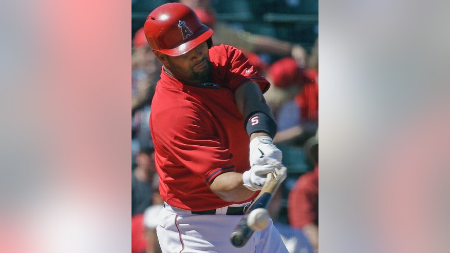 Los Angeles Angels' Albert Pujols breaks his bat as he hits a single during the fourth inning of an exhibition spring baseball game against the Cincinnati Reds, Sunday, March 9, 2014, in Tempe, Ariz. (AP Photo/Morry Gash)