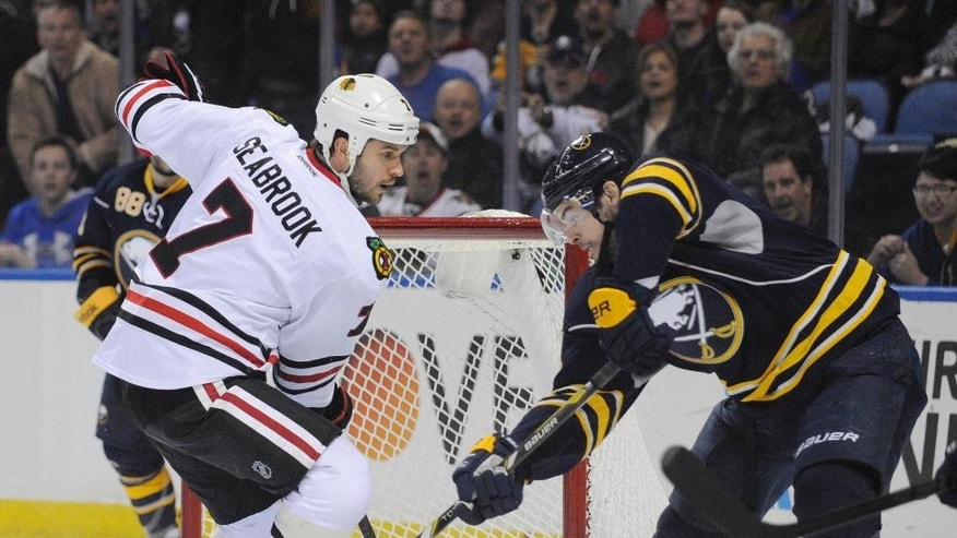 Buffalo Sabres' Drew Stafford, right, backhands the puck for a first-period goal as Chicago Black Hawks' Brent Seabrook arrives too late during the first period of an NHL hockey game in Buffalo, N.Y., Sunday, March 9,  2014. (AP Photo/Gary Wiepert)
