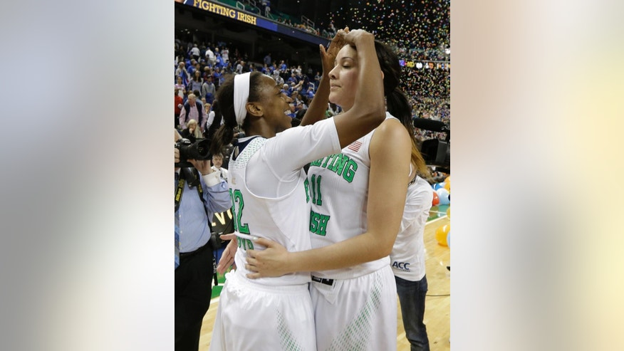 Notre Dame's Jewell Loyd (32) hugs Natalie Achonwa (11) as they celebrate after winning the NCAA college basketball championship game over Duke in the Atlantic Coast Conference tournament in Greensboro, N.C., Sunday, March 9, 2014. Notre Dame won 69-53. (AP Photo/Chuck Burton)