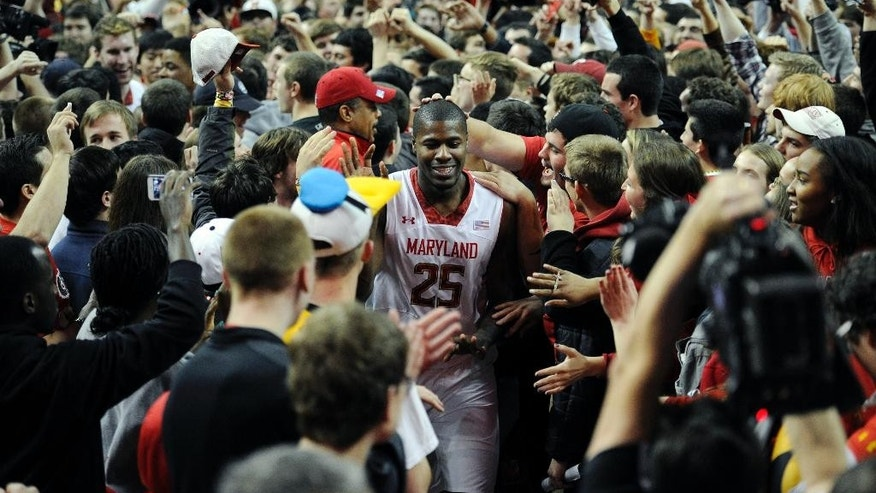 Maryland forward Jonathan Graham (25) makes his way through the crowd after Maryland fans rushed the floor after beating Virginia 75-69 in overtime of an NCAA college basketball game, Sunday, March 9, 2014, in College Park, Md. (AP Photo/Nick Wass)