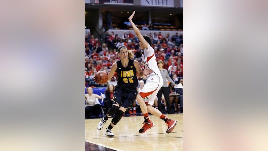 Iowa forward Kali Peschel, left, drives the base line under Nebraska guard Rachel Theriot in the first half of an NCAA college basketball game in the finals of the Big Ten women's tournament in Indianapolis, Sunday, March 9, 2014. (AP Photo/Michael Conroy)