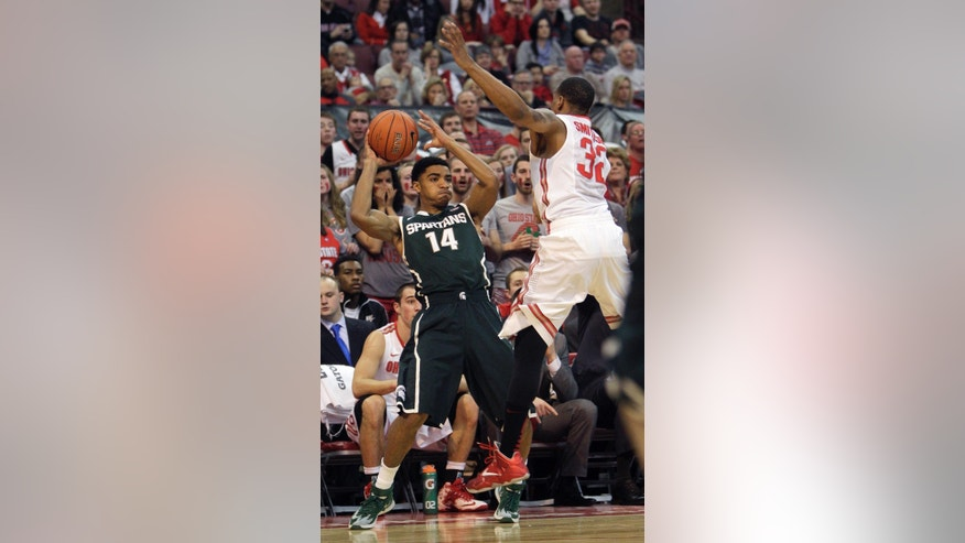 Michigan State's Gary Harris, left, looks for an open pass as Ohio State's Lenzelle Smith defends during the first half of an NCAA college basketball game Sunday, March 9, 2014, in Columbus, Ohio. (AP Photo/Jay LaPrete)