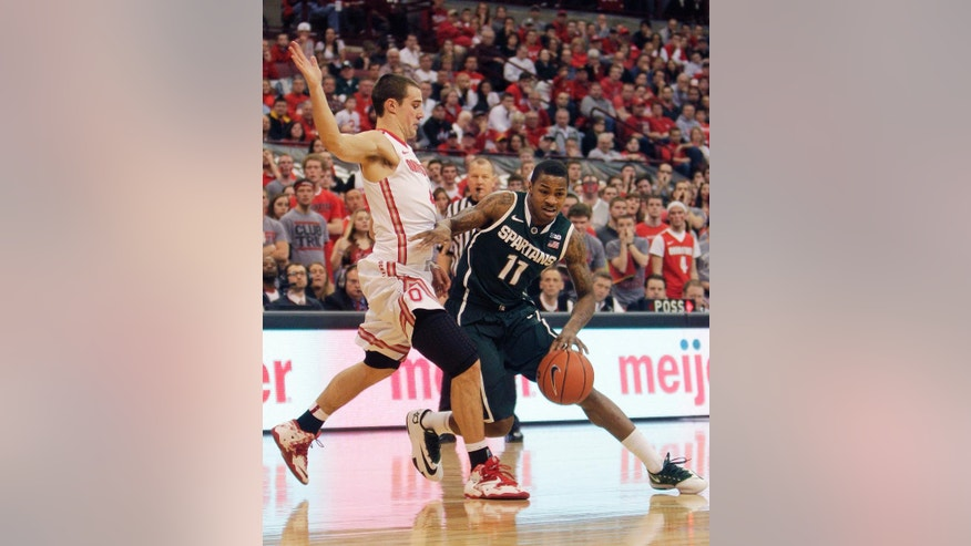 Michigan State's Keith Appling, right, tries to dribble past Ohio State's Aaron Craft during the first half of an NCAA college basketball game Sunday, March 9, 2014, in Columbus, Ohio. (AP Photo/Jay LaPrete)