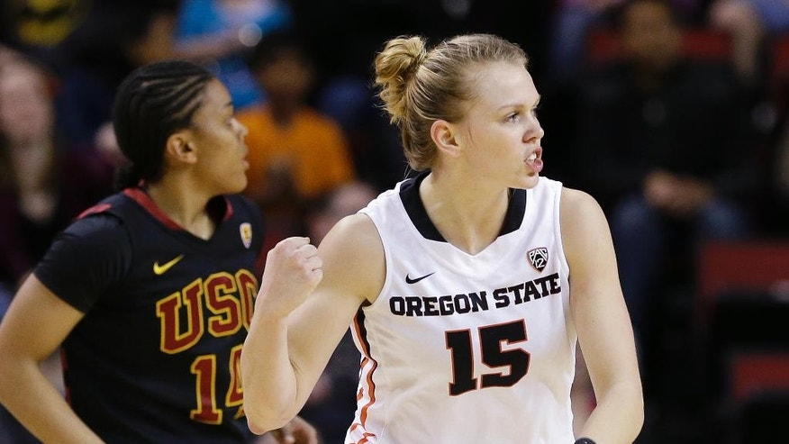 Oregon State's Jamie Weisner (15) pumps her fist after scoring as Southern California's Ariya Crook trails in the first half of the Pac-12 NCAA college championship basketball game Sunday, March 9, 2014, in Seattle. (AP Photo/Elaine Thompson)