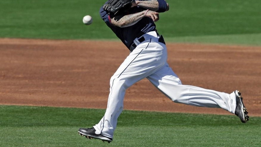 Cleveland Indians second baseman Justin Sellers makes a running throw but cannot get Milwaukee Brewers' Jean Segura on a slow ground ball in the third inning of a spring exhibition baseball game on Sunday, March 9, 2014, in Goodyear, Ariz. (AP Photo/Mark Duncan)