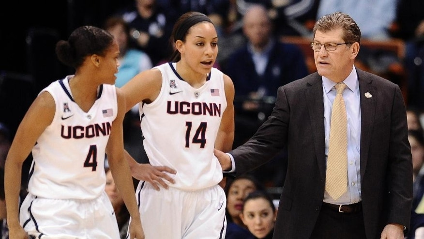Connecticut head coach Geno Auriemma, right, speaks with Moriah Jefferson, left, and Bria Hartley, center, during the first half of an NCAA college basketball game against Rutgers in the semifinals of the American Athletic Conference women's tournament, Sunday, March 9, 2014, in Uncasville, Conn. (AP Photo/Jessica Hill)