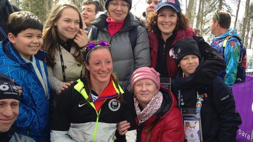 March 9, 2014: Tatyana Mcfadden of United States, second left in the first row, poses with her Russian birth mum, second right in the first row, after her race during the ladies 12km cross country ski, sitting event at the 2014 Winter Paralympic in Krasnaya Polyana, Russia.