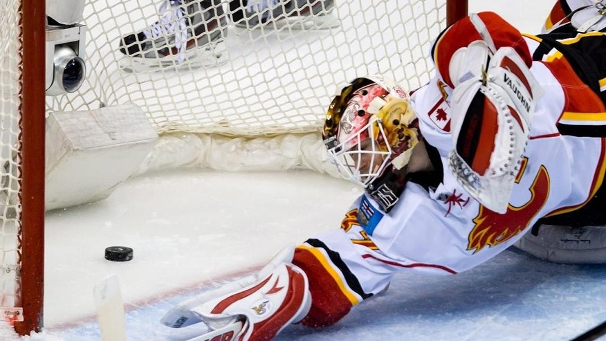 Calgary Flames' goalie Joni Ortio, of Finland, allows a goal to Vancouver Canucks' Yannick Weber, of Switzerland, during third period NHL hockey action in Vancouver, British Columbia on Saturday March 8, 2014. (AP Photo/The Canadian Press, Darryl Dyck)