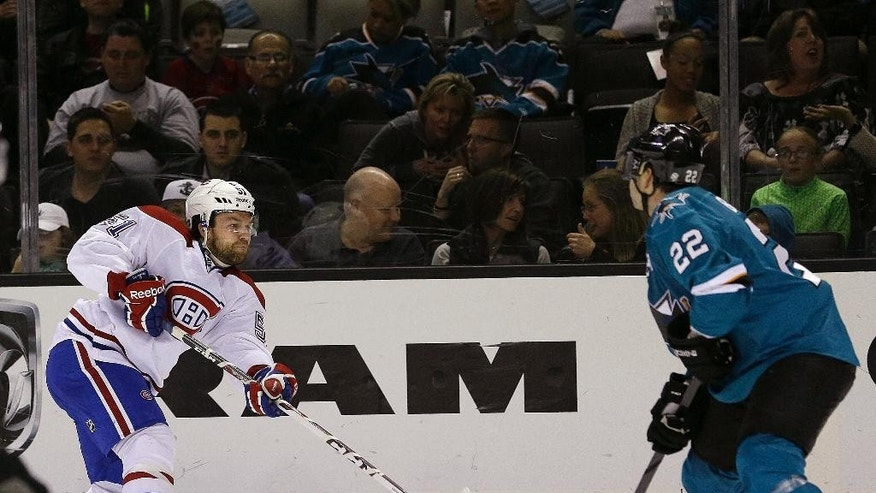 Montreal Canadiens center David Desharnais (51) takes a shot past San Jose Sharks defenseman Dan Boyle (22) during the second period of an NHL hockey game Saturday, March 8, 2014, in San Jose, Calif. (AP Photo/Tony Avelar)