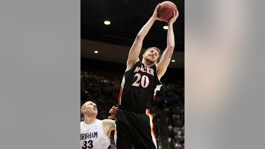 FILE - In this March 25, 2013, file photo, Mercer's Jakob Gollon (20) pulls down a rebound against BYU during a second-round game of the NIT college basketball tournament in Provo, Utah. Gollon's 153rd career game at Mercer will be his first appearance in the NCAA college tournament. (AP Photo/The Daily Herald, Spenser Heaps, File)