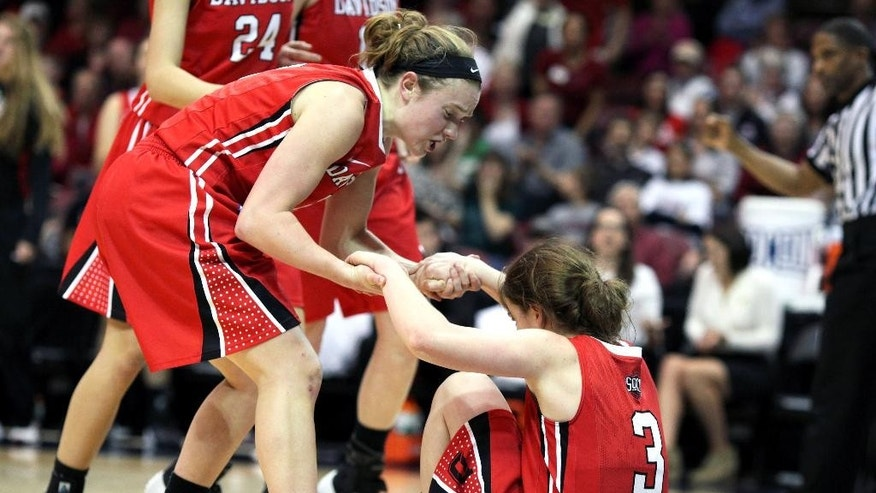 Davidson's Laura Murray (left) helps teammate Shannon Eriksson (right) up after a defensive play during the first half of the NCAA women's college basketball championship game of the Southern Conference tournament in Asheville, N.C., Monday, March 10, 2014. (AP Photo/Adam Jennings)