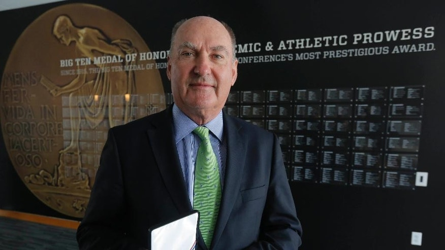 This Friday, March 7, 2014 photo shows Big Ten commissioner Jim Delany holding the Big Ten Medal of Honor that is exhibited in the The Big Ten Experience at the Big Ten conference's sparkling new headquarters in Rosemont, Ill. This year marks the 100th anniversary of the Big Ten Medal of Honor given to one male and female from each school based on their accomplishments on the field and in the classroom, and they are recognized here. The Big Ten Experience is not quite a hall of fame. It is an ode to the conference. Fans will be able to relive some of their favorite moments through a series of interactive exhibits touting its successes on the field and away from it when the museum opens in the spring or summer. (AP Photo/M. Spencer Green)
