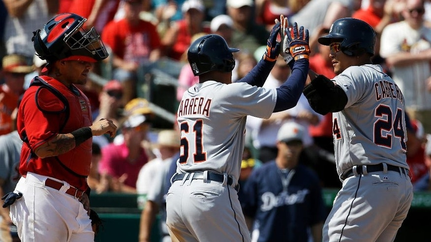 Detroit Tigers' Miguel Cabrera, right, high-fives teammate Ezequiel Carrera after hitting a two-run home run as St. Louis Cardinals catcher Yadier Molina, left, looks on in the fourth inning of an exhibition spring training baseball game, Monday, March 10, 2014, in Jupiter, Fla. (AP Photo/David Goldman)