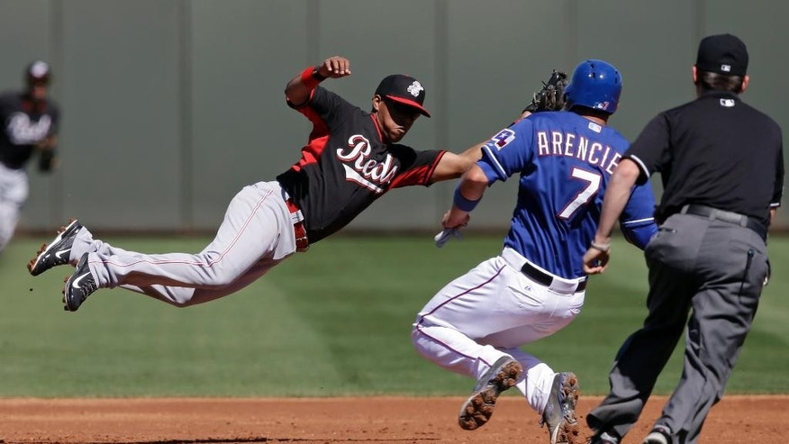 Cincinnati Reds' Ramon Santiago leaps for a throws as Texas Rangers' J.P. Arencibia steals second during the second inning of a spring exhibition baseball game Monday, March 10, 2014, in Suprise, Ariz. (AP Photo/Darron Cummings)