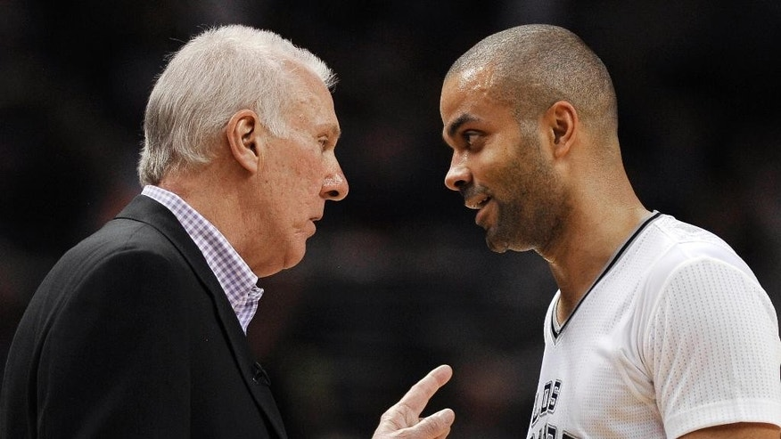 San Antonio Spurs coach Gregg Popovich, left, talks to guard Tony Parker, of France, during the second half of an NBA basketball game against the Miami Heat on Thursday, March 6, 2014, in San Antonio. San Antonio won 111-87. (AP Photo/Darren Abate)
