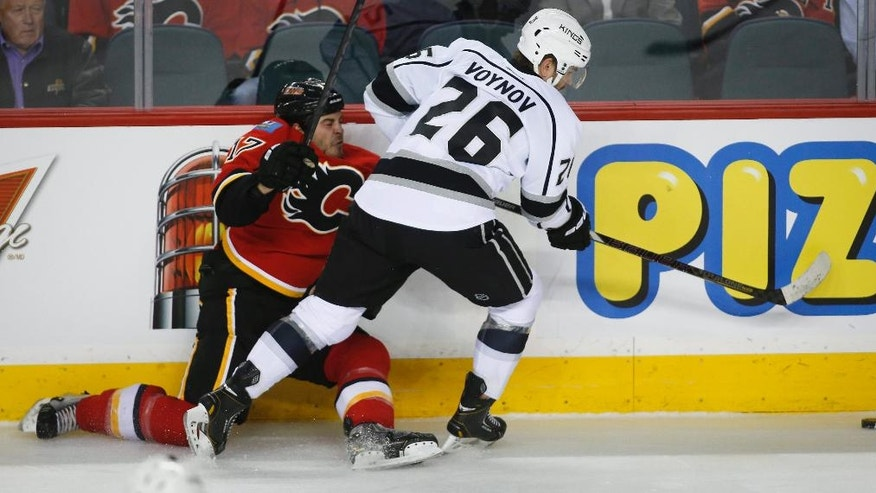 Los Angeles Kings' Slava Voynov, right, from Russia, checks Calgary Flames' Lance Bouma during the first period of an NHL hockey game in Calgary, Alberta, Monday, March 10, 2014. (AP Photo/The Canadian Press,  Jeff McIntosh)