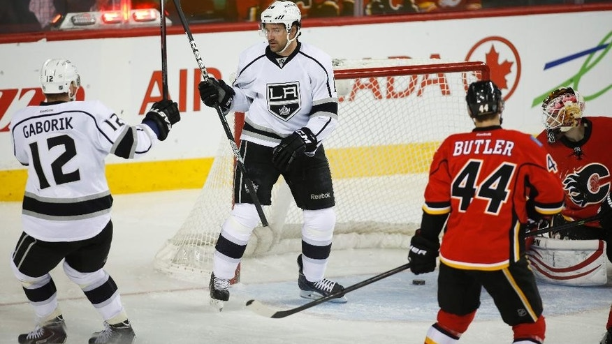 Los Angeles Kings' Justin Williams, center, celebrates his goal with teammate Marian Gaborik, left, from Slovakia, as Calgary Flames goalie Joni Ortio, right, from Finland, and Chris Butler look back at the puck during the first period of an NHL hockey game in Calgary, Alberta, Monday, March 10, 2014. (AP Photo/The Canadian Press, Jeff McIntosh)