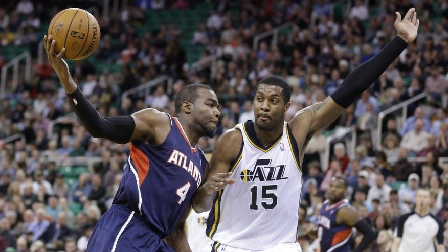 Atlanta Hawks' Paul Millsap (4) drives to the basket as Utah Jazz's Derrick Favors (15) defends in the second quarter during an NBA basketball game Monday, March 10, 2014, in Salt Lake City. (AP Photo/Rick Bowmer)