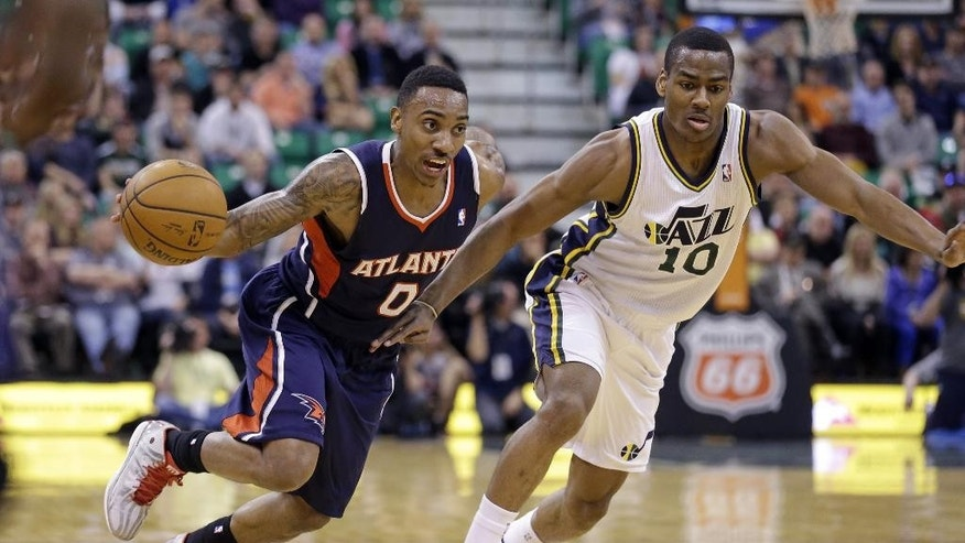 Atlanta Hawks' Jeff Teague (0) drives around Utah Jazz's Alec Burks (10) in the second quarter during an NBA basketball game Monday, March 10, 2014, in Salt Lake City. (AP Photo/Rick Bowmer)
