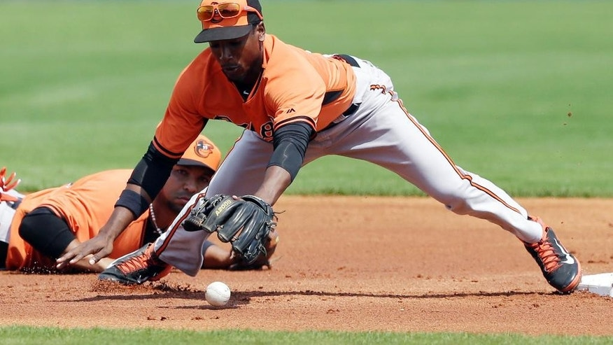 Baltimore Orioles second baseman Jemile Weeks reaches for the bobbled pitch from shortstop Alex Gonzalez, rear, during the first inning of a spring exhibition baseball game against the Pittsburgh Pirates in Bradenton, Fla., Monday, March 10, 2014. Pirates' Andrew McCutchen safely reached second. (AP Photo/Carlos Osorio)