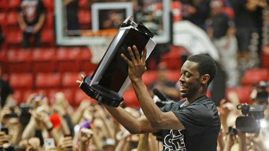 San Diego State 's Xavier Thames holds the conference trophy after State's 51-48 victory over New Mexico  that captured the Mountain West Conference regular season championship in a NCAA college basketball game Saturday, March 8, 2014, in San Diego. (AP Photo/Lenny Ignelzi)