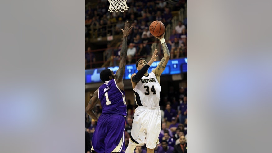 Wofford's Lee Skinner (34) drives around Western Carolina's Kenneth Hall (1) for a layup during the first half of the NCAA college basketball championship game of the Southern Conference tournament in Asheville, N.C., Monday, March 10, 2014. (AP Photo/Adam Jennings)