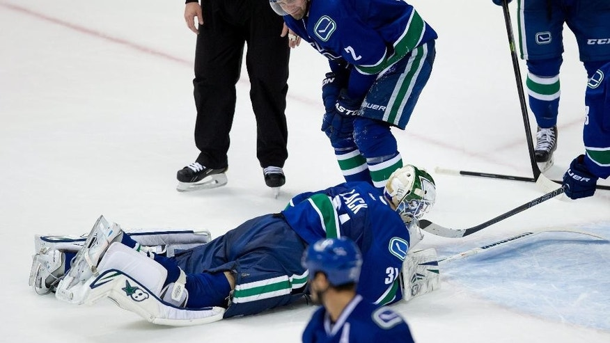 Vancouver Canucks' Dan Hamhuis, top, looks on as goalie Eddie Lack, of Sweden, lies on the ice after the New York Islanders scored their sixth goal during third period NHL hockey action in Vancouver, British Columbia, on Monday March 10, 2014. (AP Photo/The Canadian Press, Darryl Dyck)