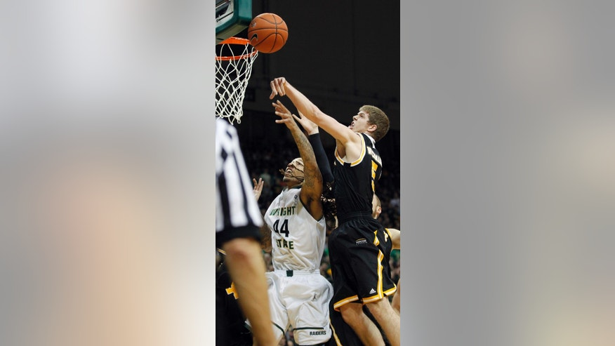 Milwaukee's Cody Whichmann, right, blocks a shot by Wright State's Tavares Sledge during the Horizon League men's tournament championship, Tuesday, March 11, 2014, in Dayton, Ohio. (AP Photo/The Dayton Daily News, Ty Greenlees)  LOCAL PRINT OUT; LOCAL TV OUT; WKEF-TV OUT; WRGT-TV OUT; WDTN-TV OUT (REV-SHARE)