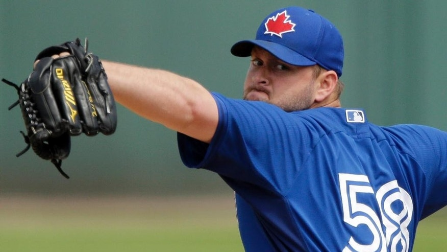 Toronto Blue Jays starting pitcher Todd Redmond throws during the first inning of a spring exhibition baseball game against the Detroit Tigers in Lakeland, Fla., Tuesday, March 11, 2014. (AP Photo/Carlos Osorio)