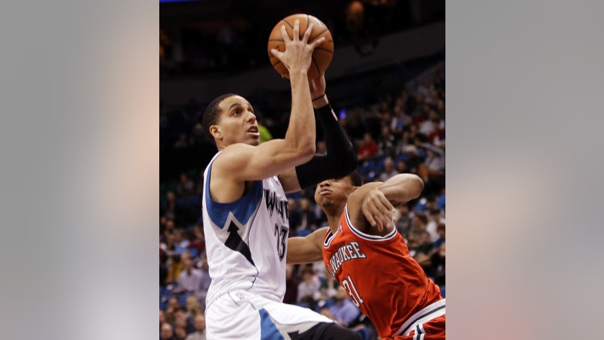 Minnesota Timberwolves' Kevin Martin lays up as Milwaukee Bucks' John Henson watches in the first quarter of an NBA basketball game, Tuesday, March 11, 2014, in Minneapolis. (AP Photo/Jim Mone)