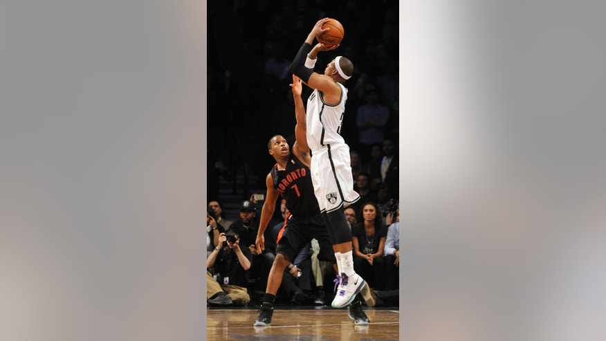 Brooklyn Nets' Paul Pierce shoots a three-pointer over Toronto Raptors' Kyle Lowry (7) that put the Nets in the lead 97-94 in the second    half of an NBA basketball game on Monday, March 10, 2014 at Barclays Center in New York. The Nets won 101-97.(AP Photo/Kathy Kmonicek)