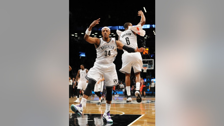 Brooklyn Nets' Paul Pierce (34) and Alan Anderson (6) celebrate Pierce's three-pointer against the Toronto Raptors that put the Nets in the lead 97-94 in the second    half of an NBA basketball game on Monday, March 10, 2014 at Barclays Center in New York. The Nets won 101-97.(AP Photo/Kathy Kmonicek)
