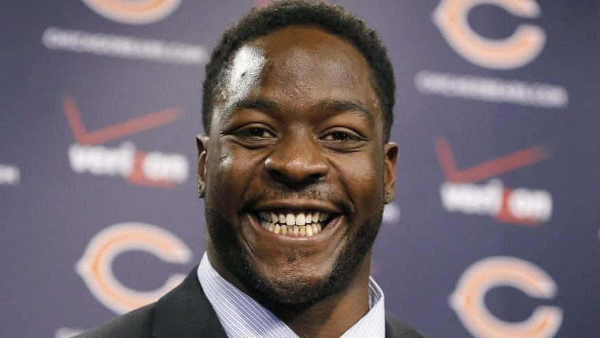 Chicago Bears defensive end Lamarr Houston smiles after being introduced as the newest member of the team during a news conference Wednesday, March 12, 2014, in Lake Forest, ill. (AP Photo/Charles Rex Arbogast)