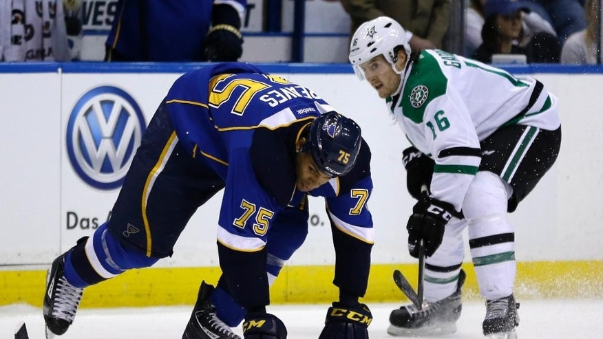 St. Louis Blues' Ryan Reaves, left, tries to control the puck as Dallas Stars' Ryan Garbutt watches during the first period of an NHL hockey game Tuesday, March 11, 2014, in St. Louis. (AP Photo/Jeff Roberson)