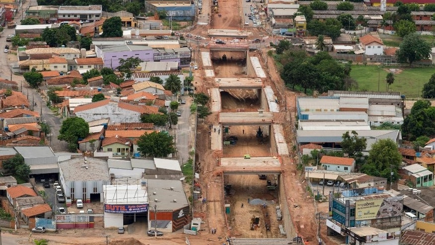"ADVANCE FOR SUNDAY, MARCH 16, 2014  AND THEREAFTER - This Dec. 12, 2013 photo released by Portal da Copa, shows an aerial view of a project, known locally as ""The Big Ditch,"" to reroute one of three main traffic arteries in Cuiaba, Brazil. It passes within a few hundred yards of the new stadium, and will hinder traffic getting to the stadium, not help it. Small business owners in the area say they were told two years ago when work began that it would be completed in a few months. They say they have lost money since then, and now can't get a straight answer as to when the work will be finished; certainly not in time for the World Cup. (AP Photo/Portal da Copa, Jose Medeiros)"