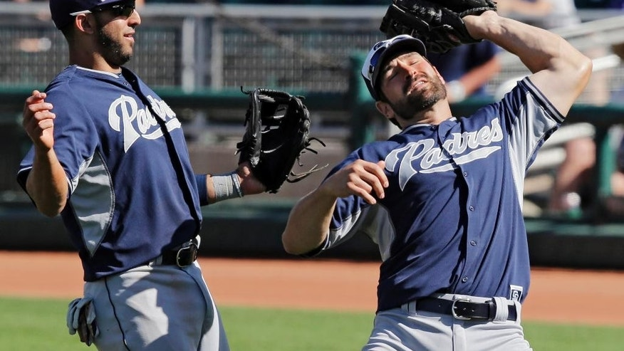 San Diego Padres first baseman Xavier Nady, right, catches a pop up by Cleveland Indians' Mike Aviles as second baseman Alex Castellanos stands near in the fifth inning of a spring exhibition baseball game Wednesday, March 12, 2014, in Goodyear, Ariz. (AP Photo/Mark Duncan)