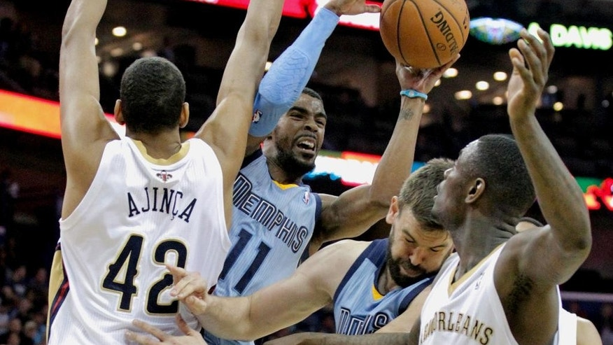 Memphis Grizzlies' Mike Conley (11) cuts through New Orleans Pelicans' Alexis Ajinca (42), Grizzlies' Marc Gasol (33) and Pelicans' Anthony Morrow (3) in the first half of an NBA basketball game in New Orleans, Wednesday, March 12, 2014. (AP Photo/Scott Threlkeld)