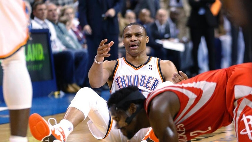 Oklahoma City Thunder guard Russell Westbrook (0) reacts after a foul by Houston Rockets guard Pat Beverley, right, during the fourth quarter of an NBA basketball game in Oklahoma City, Tuesday, March 11, 2014. Oklahoma City won 106-98. (AP Photo/Sue Ogrocki)