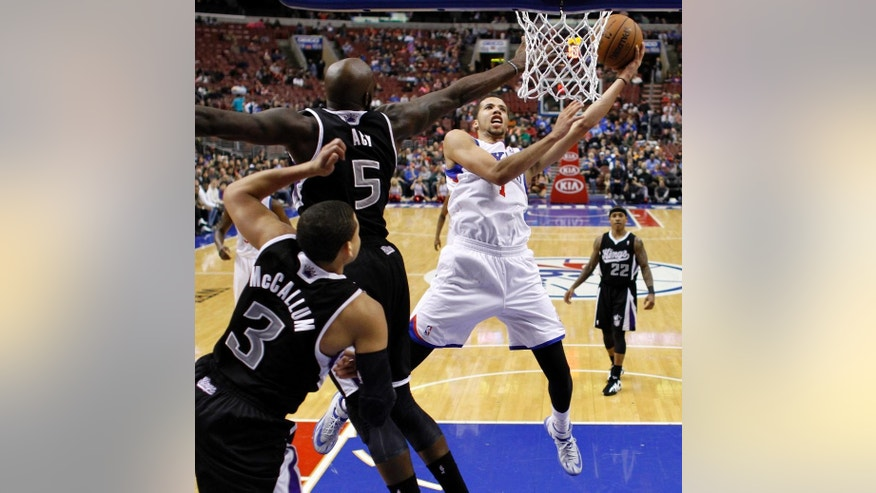 Philadelphia 76ers's Michael Carter-Williams (1) goes up to shoot against Sacramento Kings's Quincy Acy (5) and Ray McCallum (3) during the second half of an NBA basketball game on Wednesday, March 12, 2014, in Philadelphia. Sacramento won 115-98. (AP Photo/Matt Slocum)