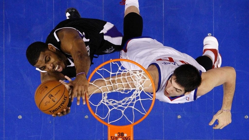 Sacramento Kings's Jason Thompson, left, goes up to shoot against Philadelphia 76ers's Byron Mullens during the first half of an NBA basketball game on Wednesday, March 12, 2014, in Philadelphia. (AP Photo/Matt Slocum)